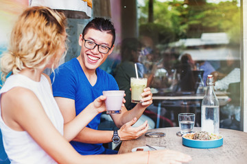 Young multiracial couple (chinese man and caucasian woman) doing cheers with healthy smoothies and talking