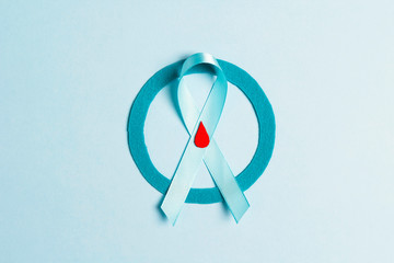 Blue circle with ribbon and drop of blood as a symbol of diabetes on a blue background.