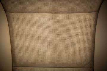 Part of leather car headrest seat details. Сlose-up beige  perforated leather car seat. Skin texture