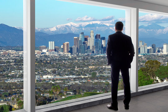 Businessman in an office looking at the view of downtown Los Angeles. The man looks like a boss or a regional manager working in California. The background is snowy San Gabriel Mountains in winter.