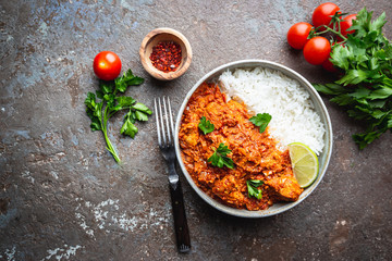 Chicken meat with tikka masala sauce, spicy curry food in a bowl with rice and seasonings, top view