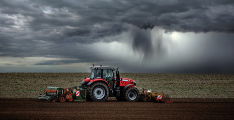 Photo sur Aluminium Marron chocolat beautiful landscape with a farmer plowing his fields before the storm
