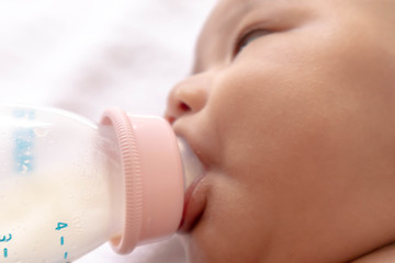 A newborn baby is eating a bottle of milk on a white bed. During bedtime, the child's brain will work. To enhance Memory-boosting and learning-building skills