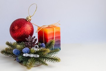 Decorative candle, red Christmas toy and fir branches on a light background. There is free space for writing text.