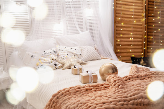 the bedroom is decorated for Christmas. the bed is covered with a soft design Merino large knitted blanket. the walls are decorated with lights of garlands.cozy gentle atmosphere of the Lodge of love