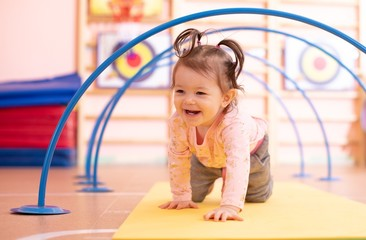 Baby toddler crawling on floor through tonnel in gym class. Lifestyle concept of children active games and exercises.