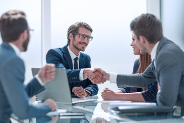 business partners reach out to each other for a handshake