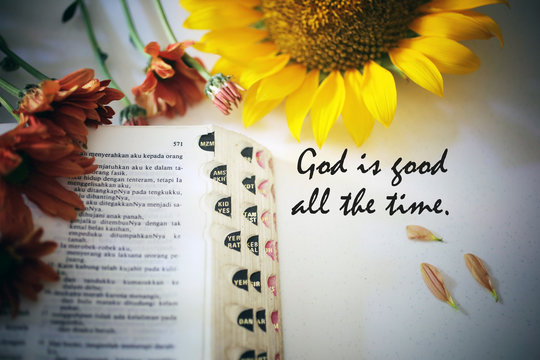 Inspirational quote - God is good all the time. With bible book open and colorful flowers arrangement on white background.
