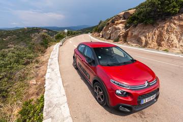 Red Citroen C3 stands on a roadside