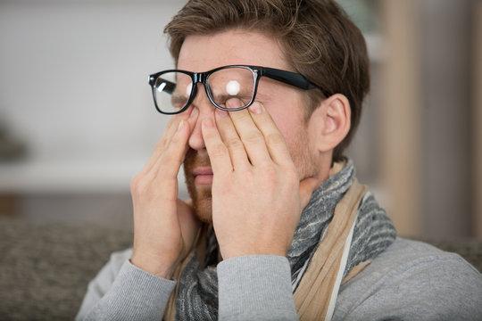a man rubbing eye at home annoying itch