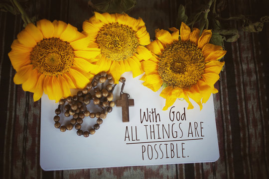 Christianity inspirational quote - With God all things are possible. With wooden Rosary, sunflowers, notebook paper arrangement background. Words of wisdom concept with Catholic symbol.