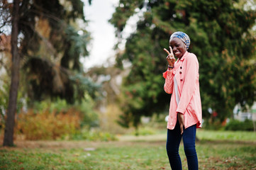 Young modern fashionable, attractive, tall and slim african muslim woman in hijab or turban head scarf and pink coat posed at park.