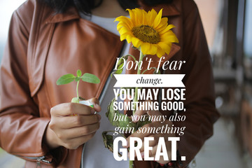 Inspirational quote - Do not fear change. You may lose something good, but you may also gain something great. With young girl hands holding sunflower plant in hand background. Words of wisdom concept