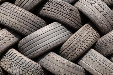 Close-up of a stack of old car tires with worn down profiles piled up in an interwoven pattern
