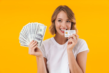 Image of excited blond woman holding money cash and credit card
