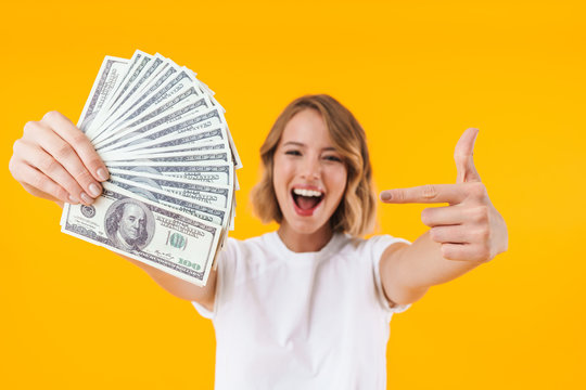 Image of excited blond woman holding bunch of money cash