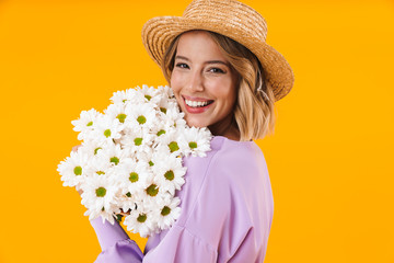 Image of optimistic woman in elegant dress and straw hat holding flowers