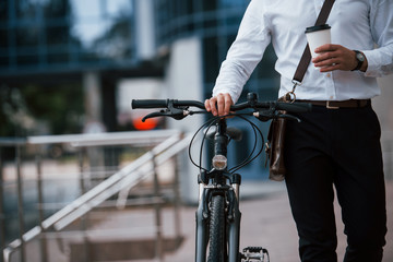 Healthy lifestyle. Businessman in formal clothes with black bicycle is in the city