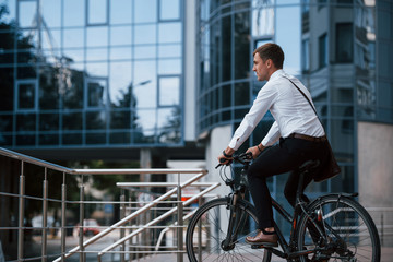 Let's ride to a job. Businessman in formal clothes with black bicycle is in the city