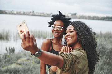 Two female afro american friends have a walk around beach. Taking selfie