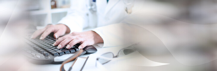 Female doctor taping on a computer keyboard; panoramic banner