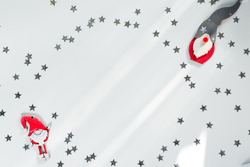 Funny handmade red gnoms in silver stars frame on white christmas background for a greeting card. Copy space flat lay