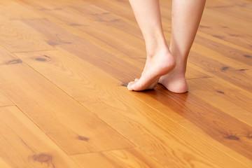 木目の床と若い女性の足元のアップ