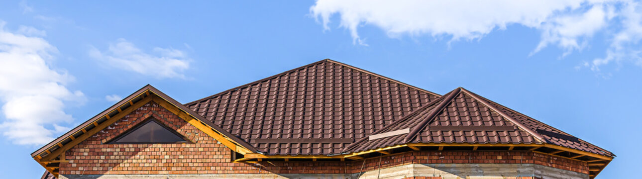The roof of the house from a metal profile against the sky with clouds