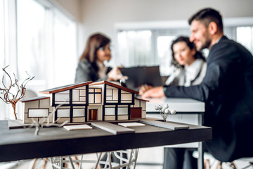 Close up image of house model with group business people on blurred background in building design studio. Architecture project concept