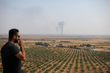Man looks on as smoke rises near the Syrian town of Ras al-Ain as seen from the Turkish border town of Ceylanpinar