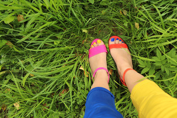 Colorful bright pedicure in different pink and orange sandals and different blue and yellow pants on a background of green grass.Fashionable summer nail art.