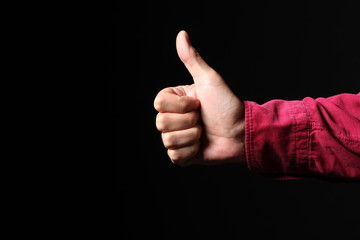 man hand makes thumb up gesture isolated on black background with copy space for your text
