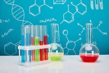 glass test tubes and flasks with colorful liquid on blue background with molecular structure