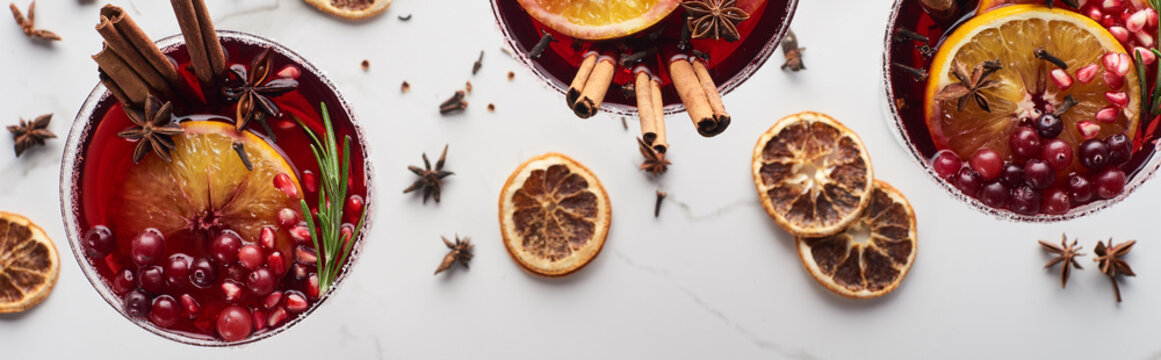 panoramic shot of christmas cocktails with orange, pomegranate, cinnamon