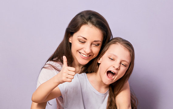 Happy excited cuddling mother and daughter shouting with wide opened mouth and showing thumb up sign on purple background with empty copy space. Natural