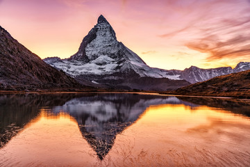 Switzerland, Matterhorn. Epic sunset view of Matterhorn mountain peak reflected in Riffelsee lake. Seasonal autumnal scenery. Picturesque Swiss landscape.