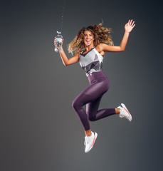 Happy joyful girl is jumping with bottle of water making splashes at photo studio on dark background.