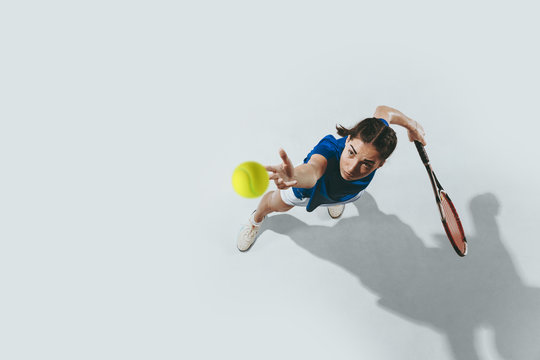 Young woman in blue shirt playing tennis. She hits the ball with a racket. Indoor studio shot isolated on white. Youth, flexibility, power and energy. Negative space. Top view.