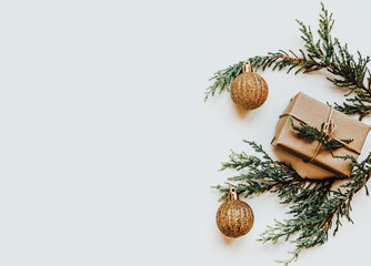 Bright green twigs of pine tree and a light brown gift box and golden balls on the white background. Isolated Copyspace christmas flat lay concept.