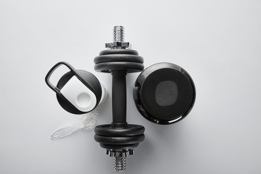 top view of spoon near protein, dumbbell and sports bottle on white