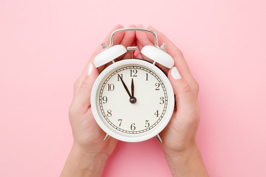 Woman hands holding white alarm clock on light pastel pink background. Time concept. Closeup.
