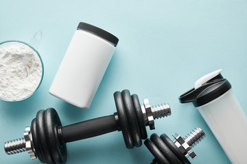 top view of dumbbells near sports bottle and protein powder on blue Fototapete