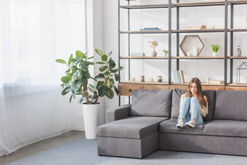 pretty girl using smartphone while sitting on sofa in living room