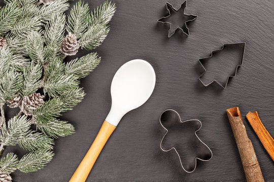 Gingerbread man, fir, snowflake cookie cutters, spoon and cinnamon sticks for Christmas cooking or baking with snowy fir branches with cones over slate background. Flat lay, top view.