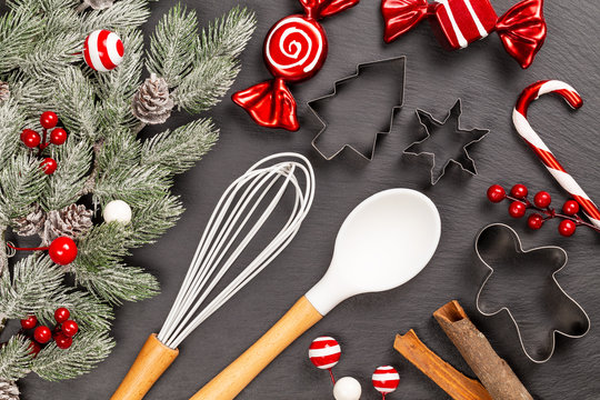 Cookie cutters with spoon, whisk, cinnamon sticks, decoration sweets, lollypops and berries for Christmas cooking or baking with snowy fir branches with cones over slate background. Flat lay, top view