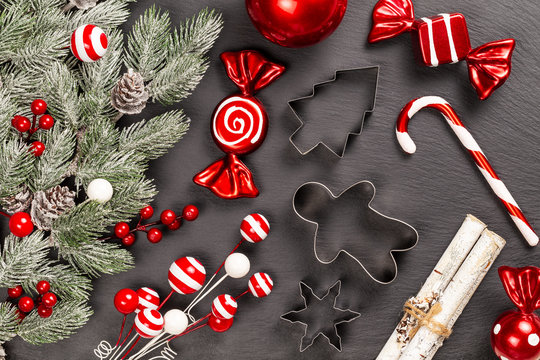Cookie cutters with candy cane, birch sticks, decoration sweets, lollipops and berries for Christmas cooking or baking with snowy fir branches with cones over slate background. Flat lay, top view.