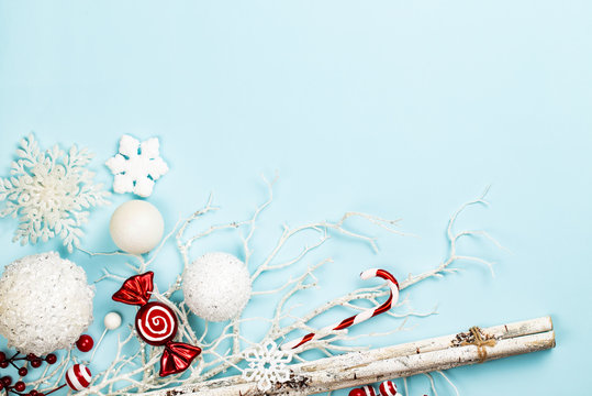 Frost like white and red christmas composition with branches, birch sticks, white spheres, decoration sweets, candy cane and snowflakes over a blue background. Flat lay, top view with copy space.