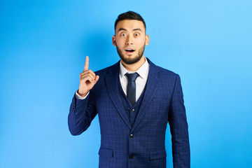 Delighted Asian Kazakh businessman has an idea, raised index finger with open mouth in a suit and tie in blue studio isolated
