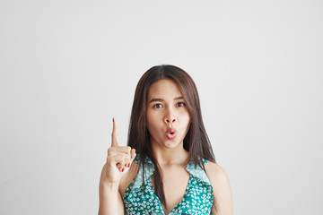 Clever Thai asian student girl raised index finger inspiredly, has an idea, knows something special isolated with copy space on white wall