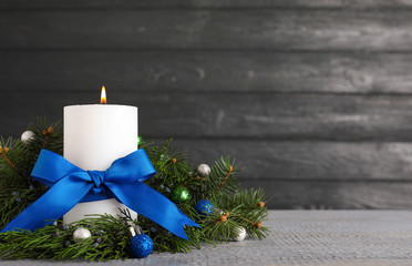 Fotobehang - Burning white candle with Christmas decor on wooden table against dark background. Space for text
